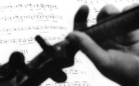 En hand omsluter en violinhals och i bakgrunden finns ett notblad