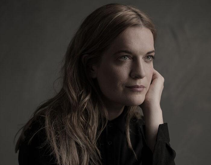 Porträttfotografi av den brittiska sopranen Ruby Hughes mot en mörkgrå bakgrund