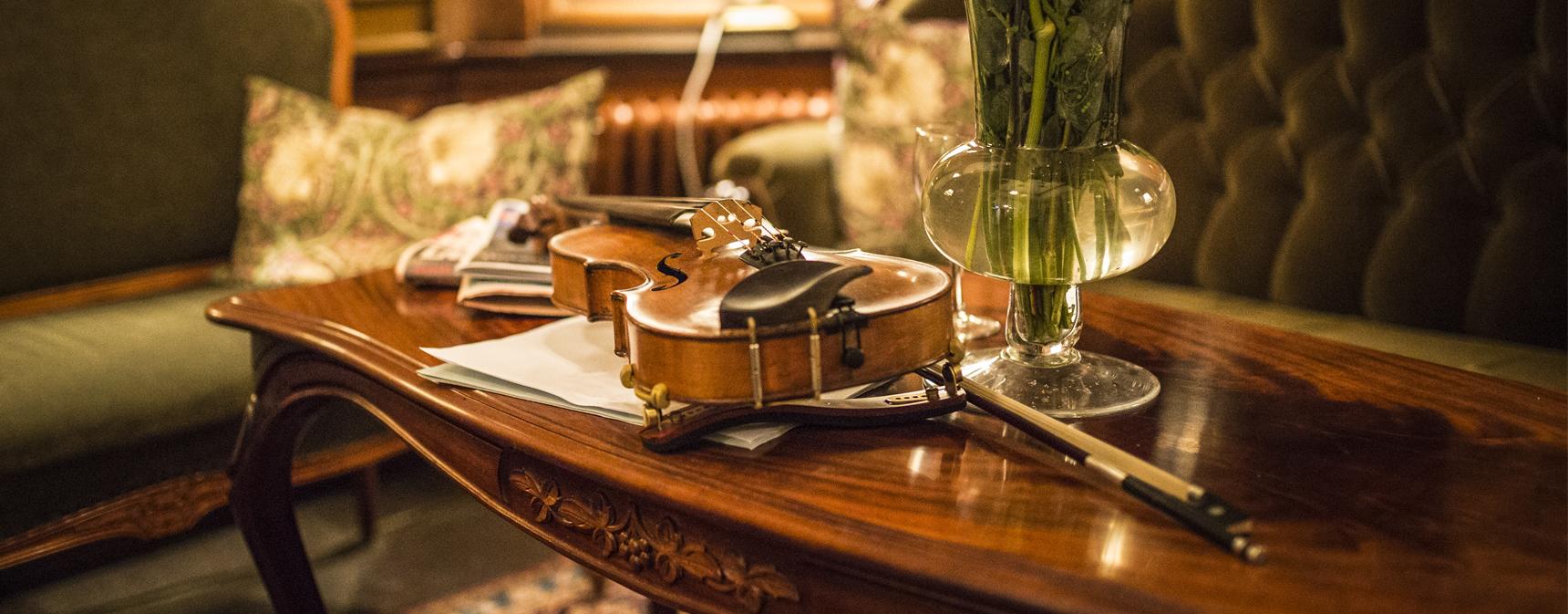 En violin och en stråke liggande på ett träbord